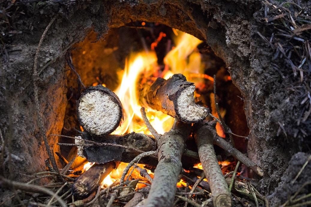 """Alt træ i området var gennemvædet og stort set umuligt at få ild i. Det tog i hvert fald en halv time førend der var anstændige flammer. Ilden trækker sig baglæns pga. trækket i """"skorstenen"""" så udfordringen består i at få indgangshullet varmet op så man kan fyre der. Det er samtidig det der skal fungerer som ovn."""
